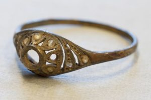 In this photo made available by the Auschwitz Museum in Oswiecim, Poland on Friday, 20 May 2016, a Polish-made golden ring is displayed . A spokesman for the Auschwitz Museum says a Polish-made golden ring and chain have been found hidden under the false base of an enameled mug that must have belonged to a victim of the Nazis' death camp. (www.auschwitz.org via AP)